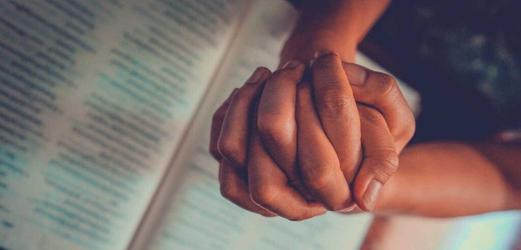 Manos juntas de una mujer que ora sobre la Biblia