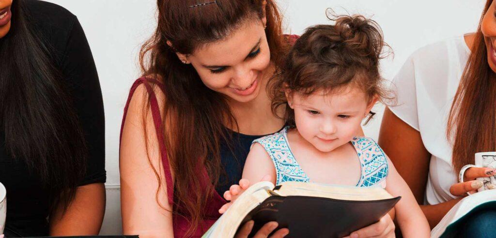 Mujer sonriente lee la Biblia con su hija pequeña sobre sus rodillas